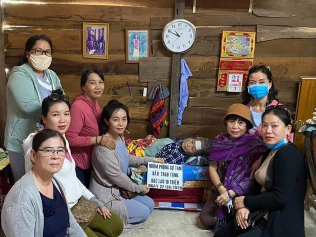 Nhóm thiện nguyện trao tiền cho bà Lan đang nằm tại nhà.jpg
