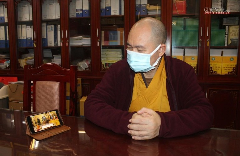 Thượng tọa Thích Đức Thiện, Phó Chủ tịch kiêm Tổng Thư ký Hội đồng Trị sự GHPGVN xem lễ cầu an online qua thiết bị điện thoại di động - Ảnh: Chu Minh Khôi