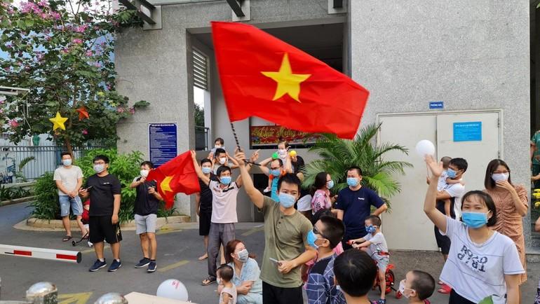 Cư dân chung cư Felix homes 44 Nguyễn Văn Dung, phường 6 quận Gò Vấp cầm lá cờ Việt Nam reo hò hạnh phúc khi rào chắn phong tỏa đã được gỡ bỏ - Ảnh: TTYT quận Gò Vấp