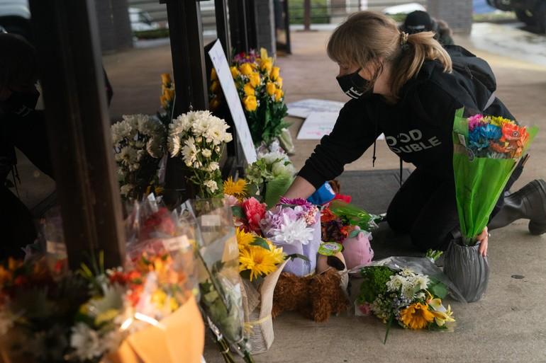 Một phụ nữ đặt hoa tưởng niệm 8 phụ nữ gốc Á bị sát hại ở Atlanta - Ảnh: Getty Images
