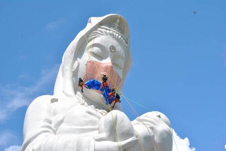 Nhiều ý kiến về việc đeo khẩu trang cho tượng Bồ-tát Quán Thế Âm - Ảnh: CBS