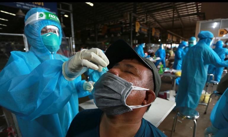 Nhân viên y tế lấy mẫu xét nghiệm Covid-19 tại chợ đầu mối Bình Điền