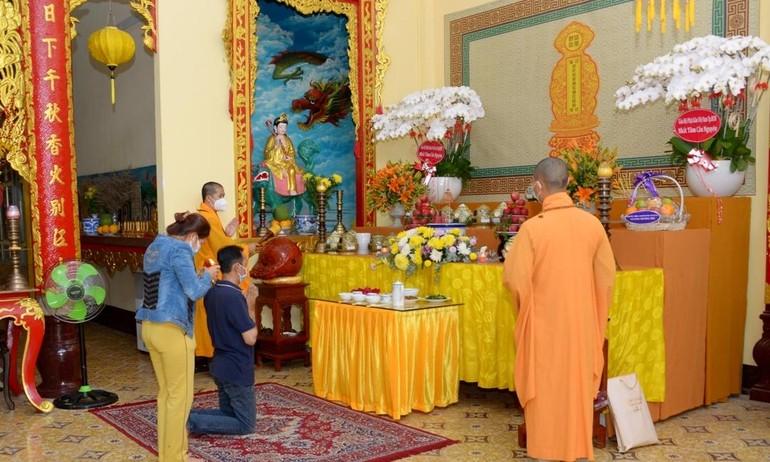 Gia đình cô Hồ Thị Thu Thủy ( phường 1, quận 3) cúng hương linh người thân tại chùa Long Hoa sáng 14-8 - Ảnh: Bảo Toàn