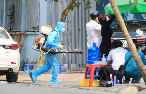 Tiến hành phun khử khuẩn trong lẫn ngoài tòa chung cư bị phong tỏa tại quận Gò Vấp trưa 8-2 - Ảnh: Nhật Thịnh/ TTO