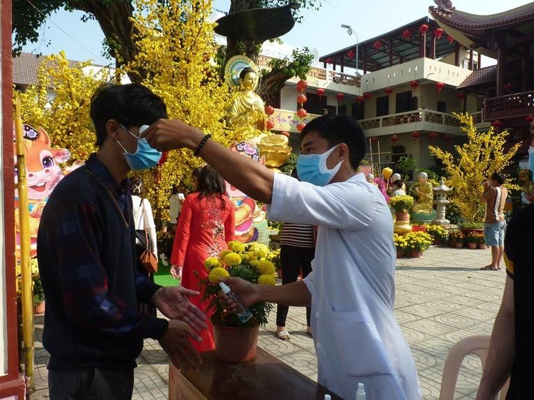 Trước khi vào chùa, Phật tử được đo thân nhiệt, nhắc khẩu trang
