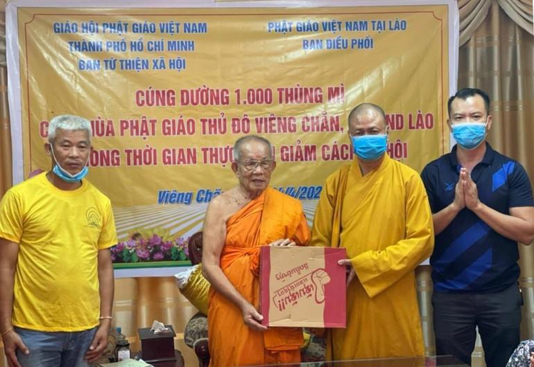 Thượng tọa Thích Minh Quang, đại diện Ban Từ thiện xã hội GHPGVN TP.HCM trao quà đến Hòa thượng Bounma Symaphom - Ảnh: C.Phật Tích