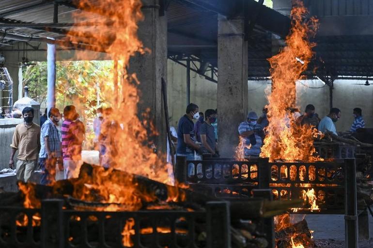 Người nhà đứng gần những giàn hỏa thiêu thi thể bệnh nhân Covid-19 ở thành phố Virar ngày 23-4.
