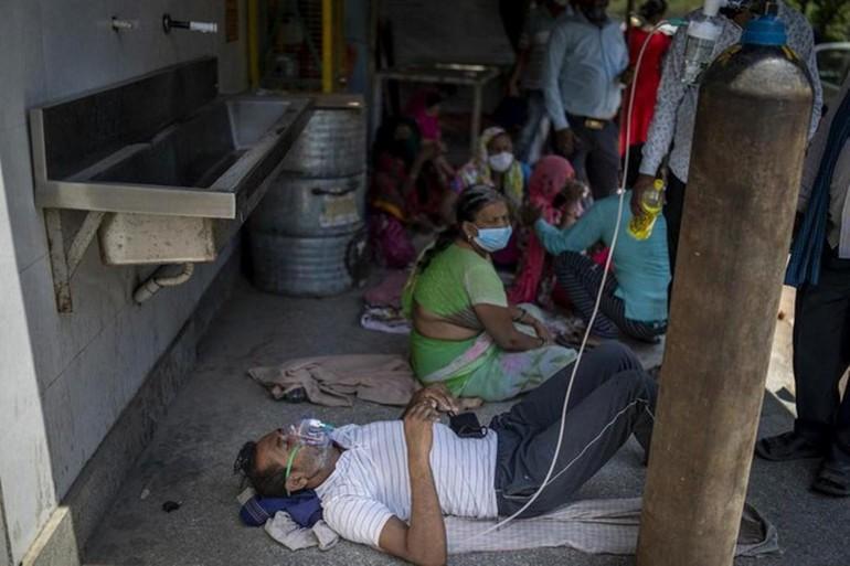 Một bệnh nhân Covid-19 thở oxy trong lúc chờ giường bệnh ở New Delhi, Ấn Độ hôm 24-4 - Ảnh: AP