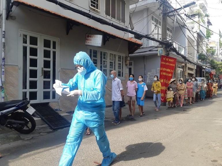 Nhân viên y tế khẩn trương làm thủ tục xét nghiệm cho người dân tại phường 15, quận Bình Thạnh - Ảnh: HCDC
