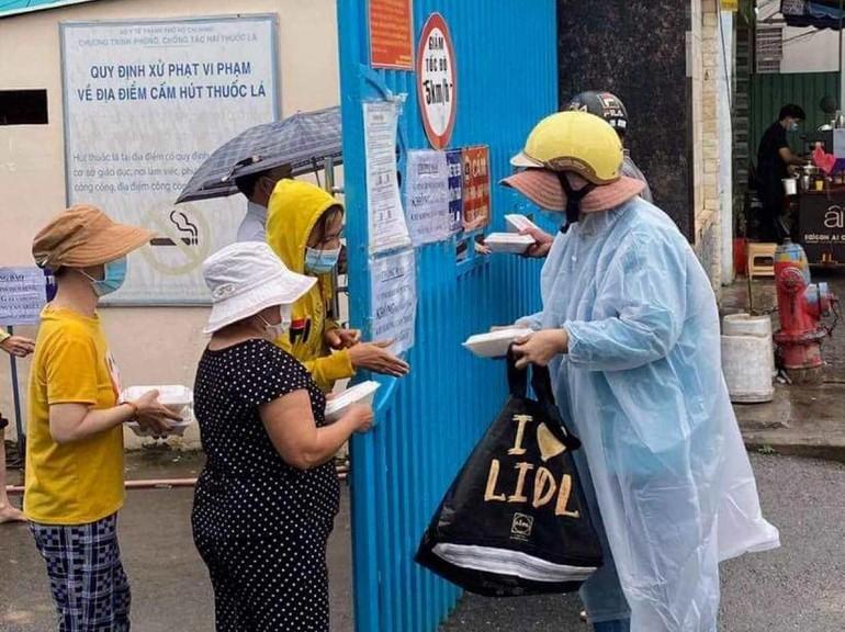 Tình nguyện viên tặng suất cơm chay đến thân nhân bệnh nhân tại cổng một bệnh viện - Ảnh: T.N