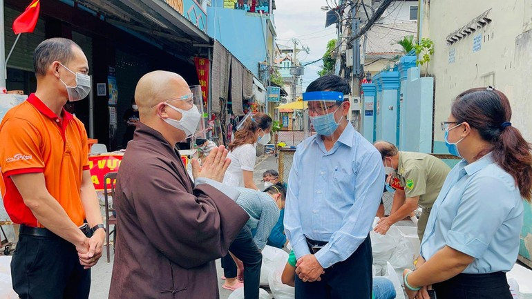 Thượng tọa Thích Trí Thông, Phó trụ trì chùa Viên Giác trao đổi với cán bộ khu cách ly để giúp đỡ người dân khó khăn - Ảnh: V.Gi