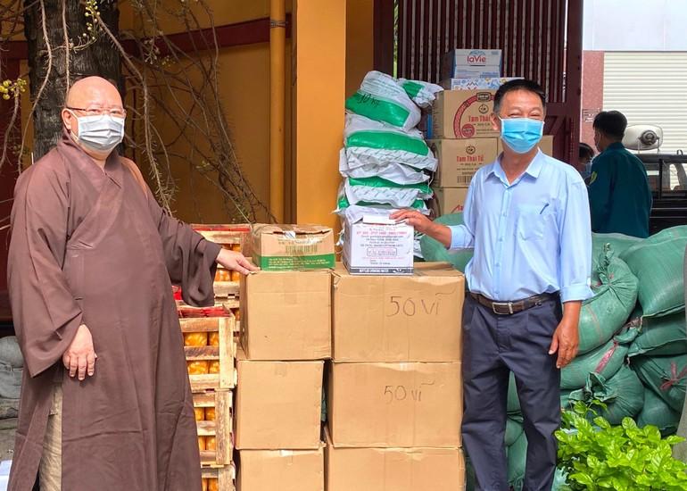 Thượng tọa Thích Đồng Văn trao quà đến Chủ tịch UBTTVN phường 1 để chuyển quà đến người dân khu cách ly - Ảnh: V.Giác