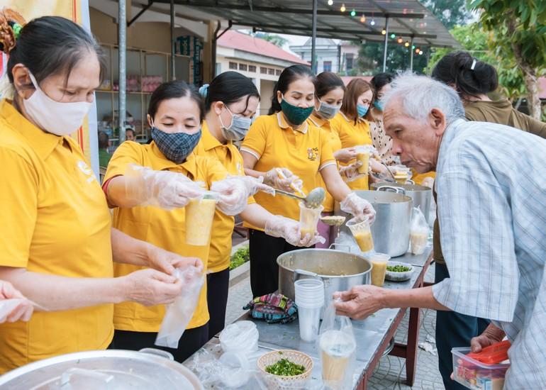 Các tình nguyện viên trao suất cháo đến bệnh nhân nghèo