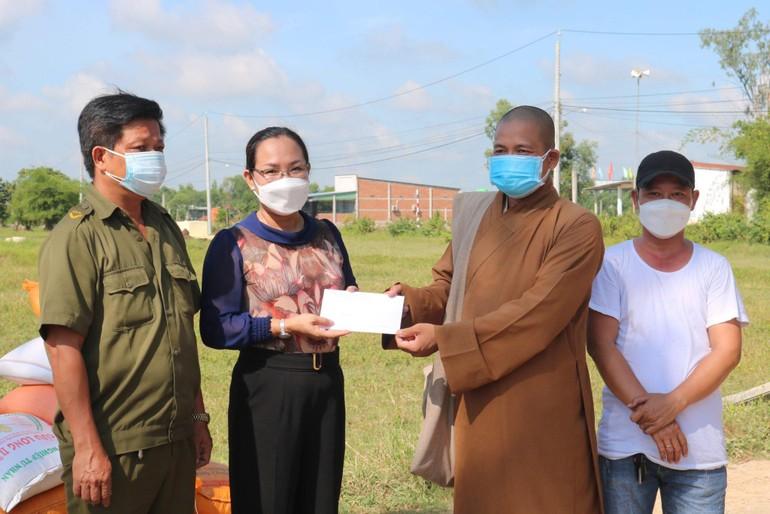 Đại đức Thích Lê Duyên trao quà đến bà Nguyễn Thị Thu Hà, Phó Chủ tịch UBND xã Hiệp Hòa để hỗ trợ người dân
