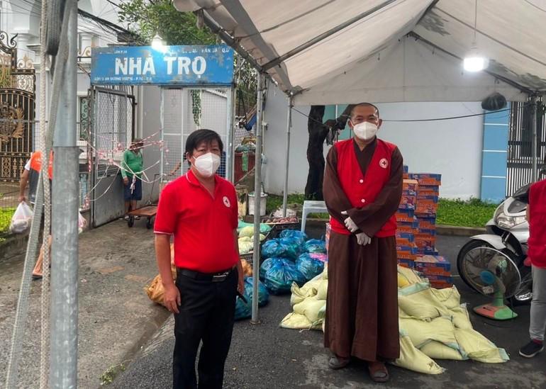 Thượng tọa Thích Lệ Quang, trụ trì chùa Vạn Liên cùng Chủ tịch Hội Chữ thập đỏ quận 8 trao quà tại nhà trọ