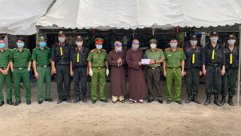 Hòa thượng Thích Huệ Thông trao quà, động viên lực lượng kiểm dịch tại chốt kiểm dịch thuộc Trại giam Bố Lá - Ảnh: PGBD