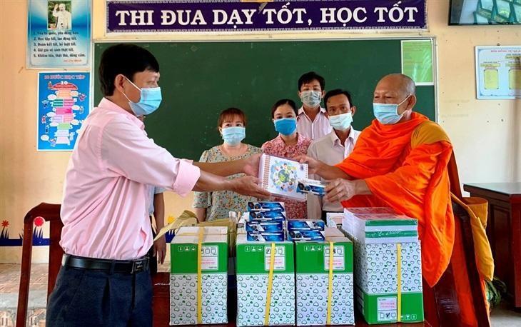 Đại diện Trường Tiểu học 2, xã Định Hòa tiếp nhận quà cho học sinh khó khăn của trường - Ảnh: CTV