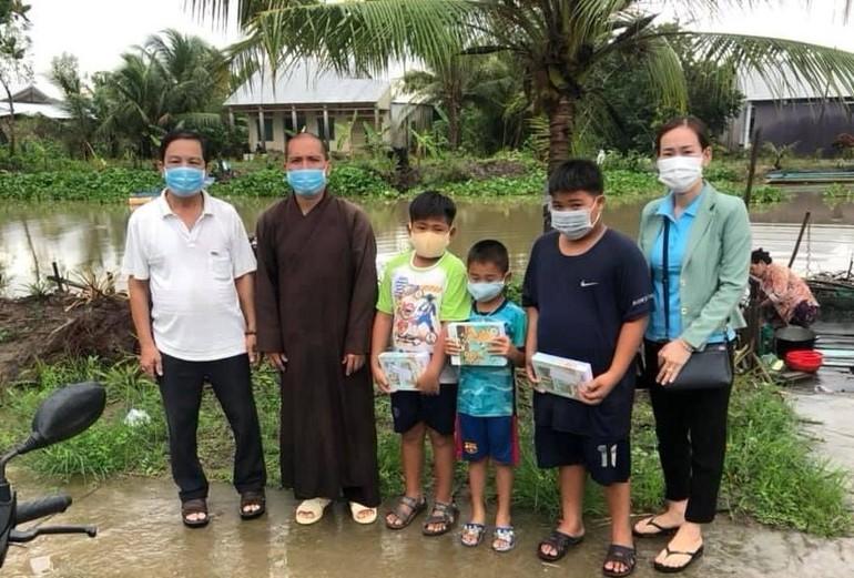 Đại đức Thích Minh Kính, trụ trì chùa Dân An cùng đại diện địa phương trao tập cho các em học sinh