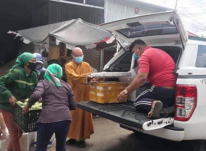 Đại đức Thích Nhuận Độ cùng bà con Phật tử người đồng bào đóng thùng rau củ gửi đến Sài Gòn - Ảnh: NA