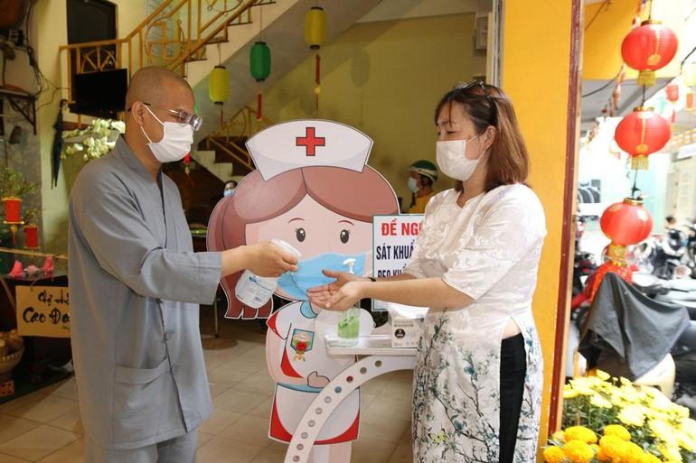 Phật tử rửa tay sát khuẩn trước khi vào lễ Phật