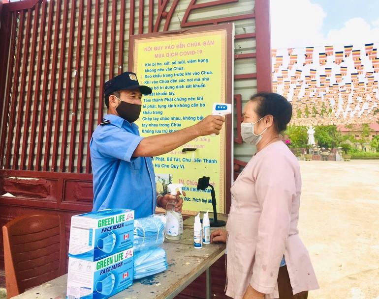 Kiểm tra thân nhiệt trước khi vào chùa Chí Linh, huyện Yên Thành, Nghệ An