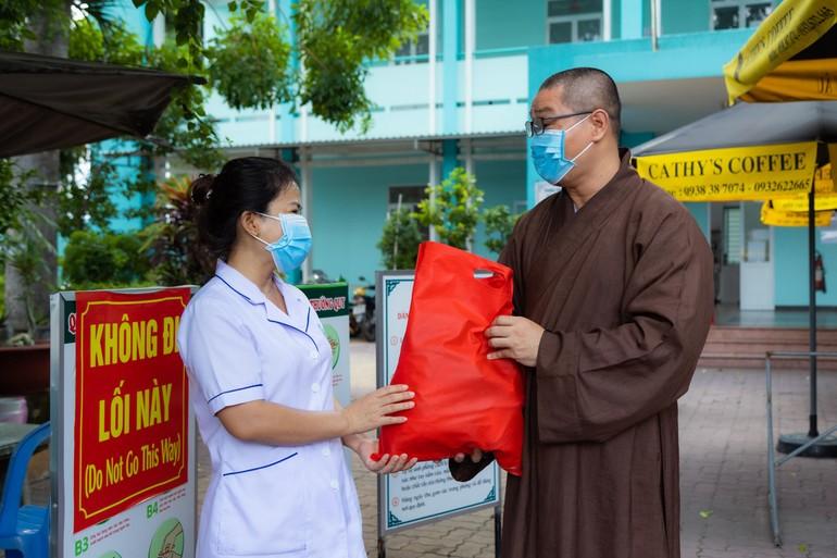 Đại đức Thích Minh Thuận đại diện Quỹ Đến Từ Trái Tim tặng quà lực lượng bảo vệ chốt chống dịch và y tế tại các nơi cách ly trên địa bàn quận Tân Phú.