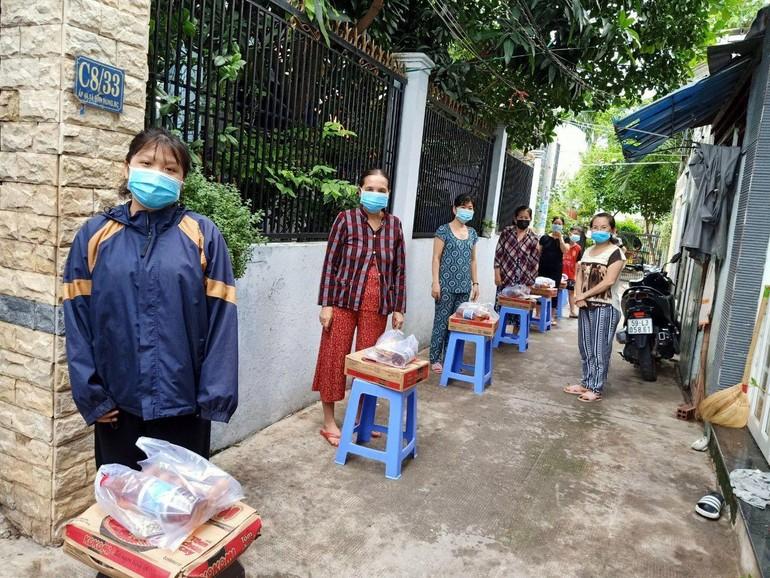 Người dân ở khu vực phong tỏa hẻm C8, đường Phạm Hùng, huyện Bình Chánh nhận quà hỗ trợ