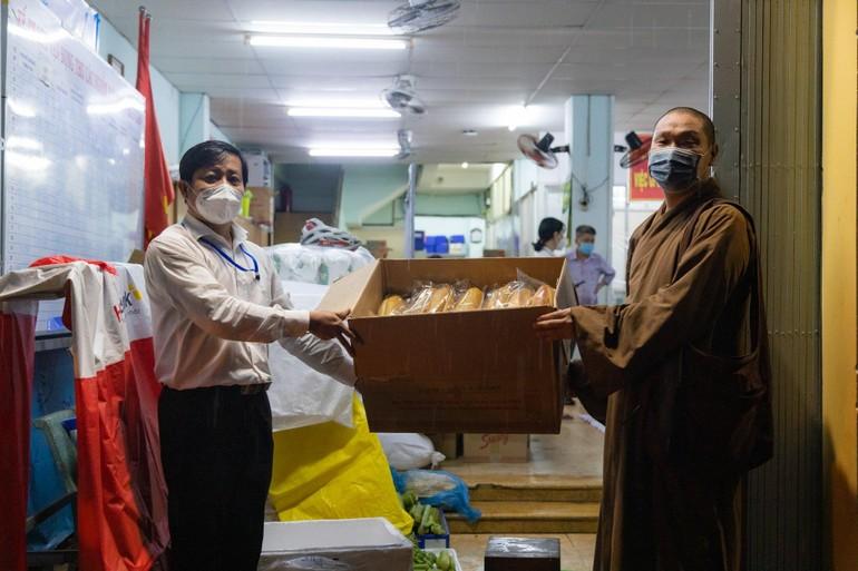 Đại đức Thích Minh Thuận đại diện cựu Tăng Ni sinh khóa V trao quà, nâng đỡ người yếu thế vượt qua giai đoạn khó khăn của dịch bệnh - Ảnh: Phùng Anh Quốc
