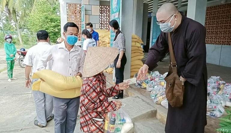 Đại đức Thích Hạnh Huệ tặng quà cho bà con tại UBND xã Huyền Hội