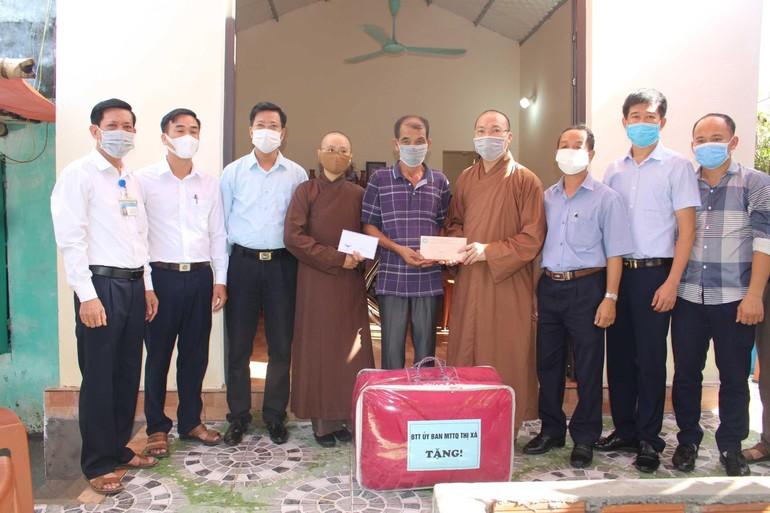 Thượng tọa Thích Thanh Lịch, Phó trưởng ban Trị sự GHPGVN tỉnh Quảng Ninh, đại diện chính quyền trao hỗ trợ cho gia đình ông Vũ Văn Thanh - Ảnh: TĐH