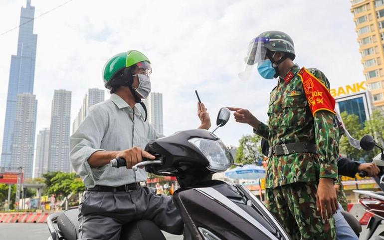 """Người dân trình mã QR khi khai """"di chuyển nội địa"""" tại chốt kiểm soát ở quận Bình Thạnh - Ảnh: Quỳnh Trần"""