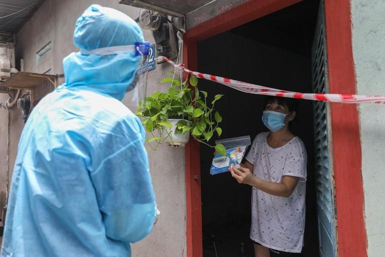 Nhân viên y tế phường 3, quận 8 đến thăm khám, tặng thuốc cho người mắc Covid-19 đang điều trị tại nhà, ngày 29-8 - Ảnh: Quỳnh Trần
