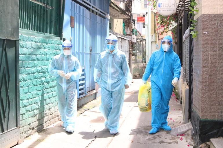 Đội thăm khám bệnh nhân F0 tại nhà gồm 1 bác sĩ quân y, 1 bác sĩ trạm y tế và 1 tình nguyện viên mang theo túi đựng trang thiết bị, vật dụng y tế như: máy đo SpO2, kít test nhanh, khẩu trang, đồ bảo hộ... - Ảnh: Nguyễn Thuận