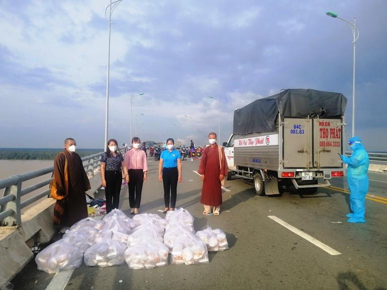 Chùa Bình Phước hỗ trợ cơm cho người dân từ vùng dịch trở về quê tại chốt cầu Cổ Chiên